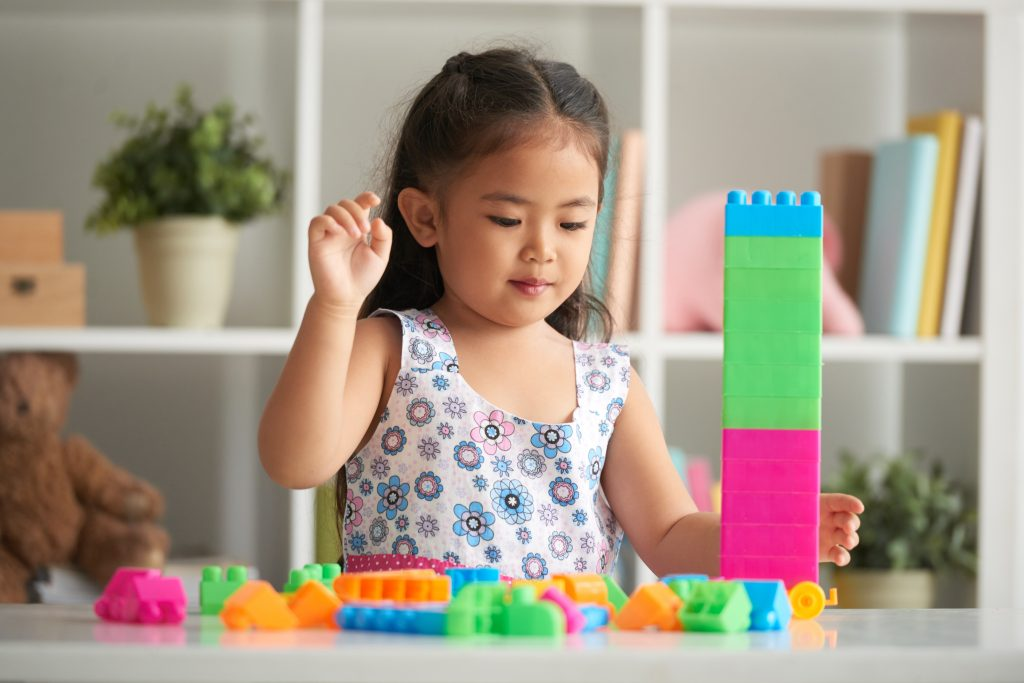 Little girl building with bright plastic cubes